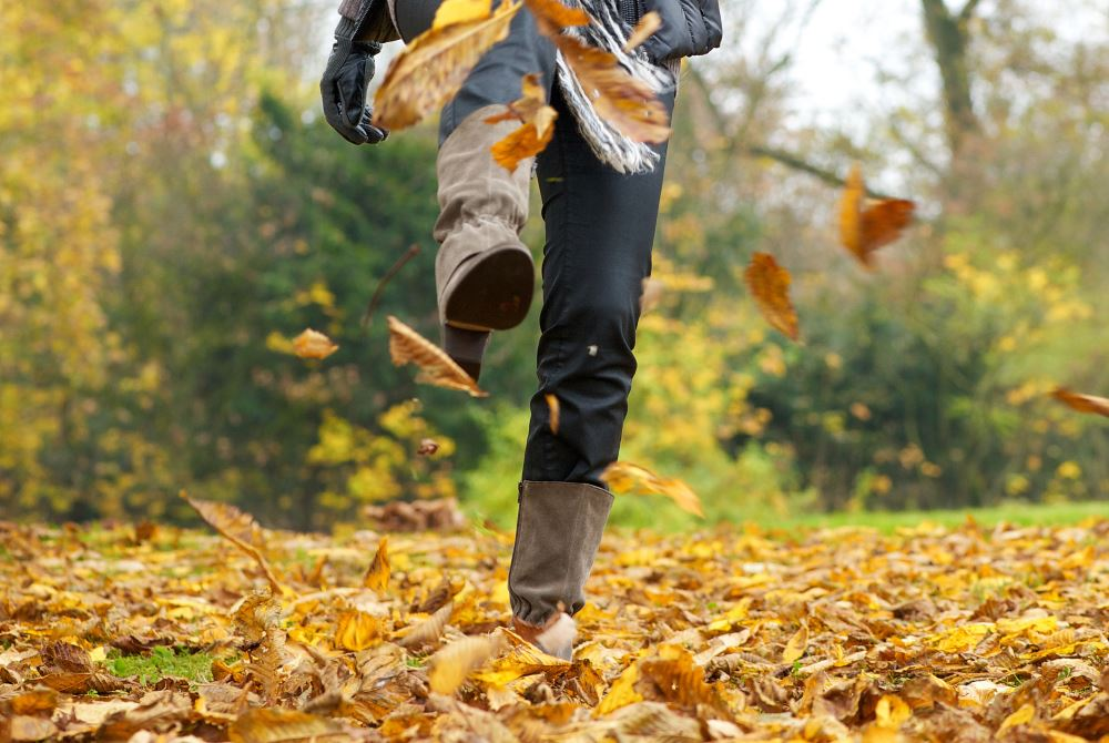 Woman kicking up Autumn leaves in a pair of boots