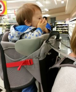 Baby in a backpack carrier - hands over his mouth