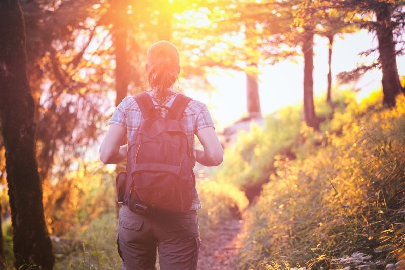 Woman hiking into the sunset - best hiking hacks