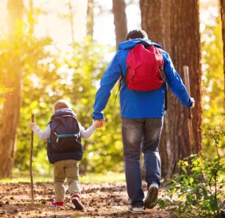 Father and child hiking together while using sticks